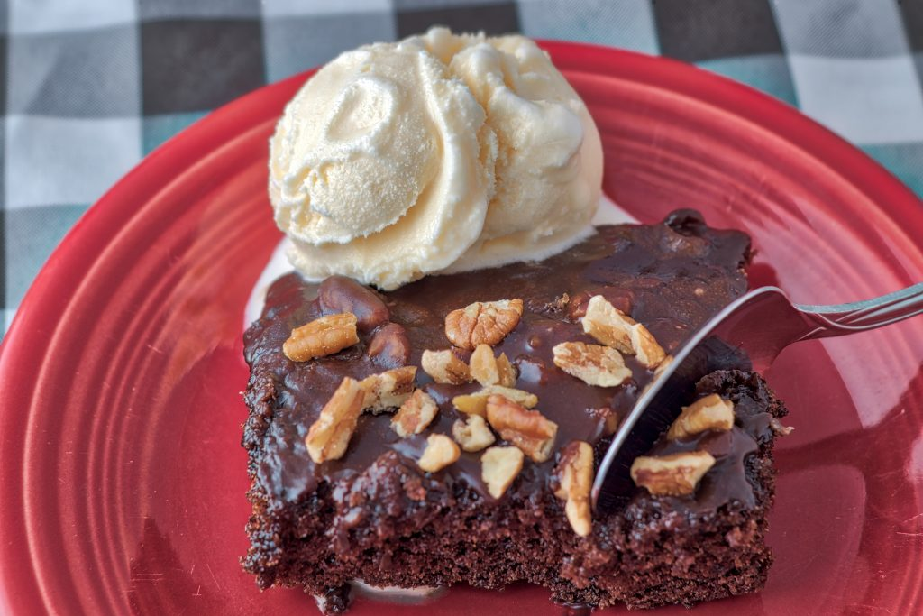 Slice of Texas sheet cake on a red plate with pecans on top and a scoop of vanilla ice cream in the background. When deciding what to eat in Texas, be sure to give this cake a try!