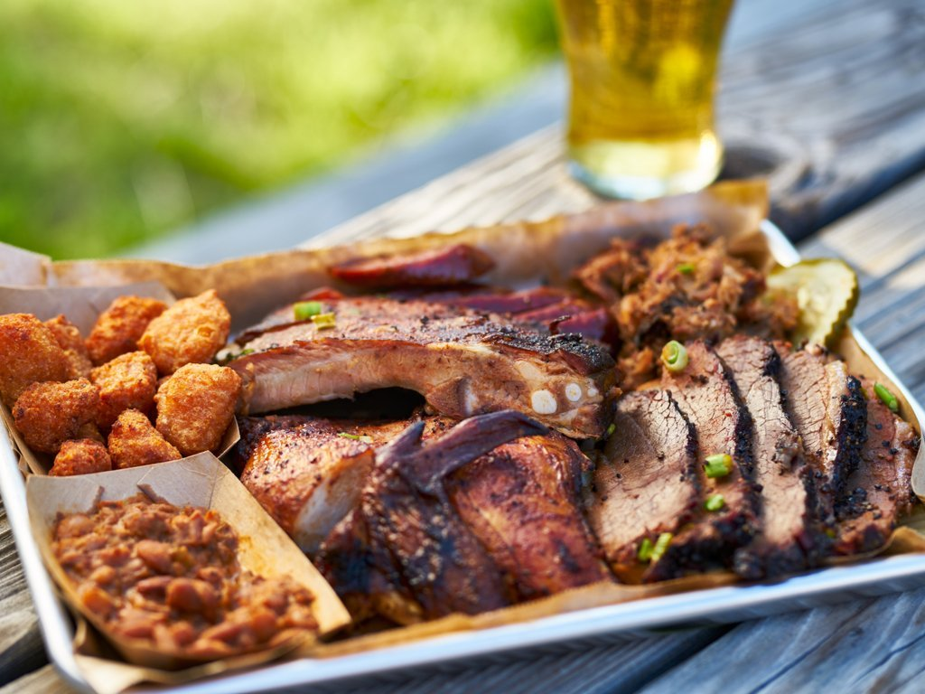 Plate of Texas barbecue served on a picnic table outside with a beer in the background. Barbecue is an important Texas food group!