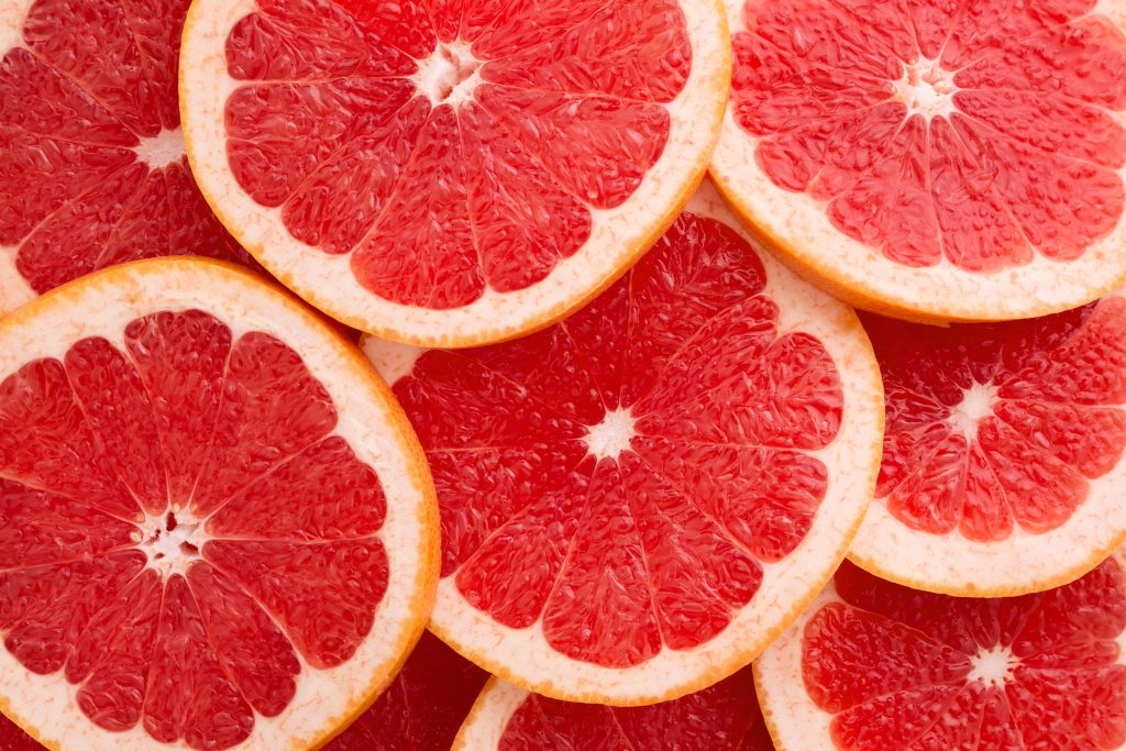 Red grapefruits cut in half and piled on top of each other