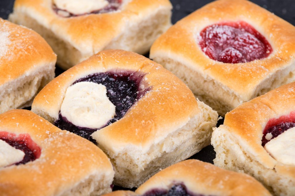 Texas kolaches arranged on a tray with fruit and cheese on top