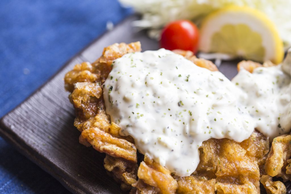 Chicken Fried steak with white gravy on top on a blue background. Chicken fried steak is popular in Texas cuisine
