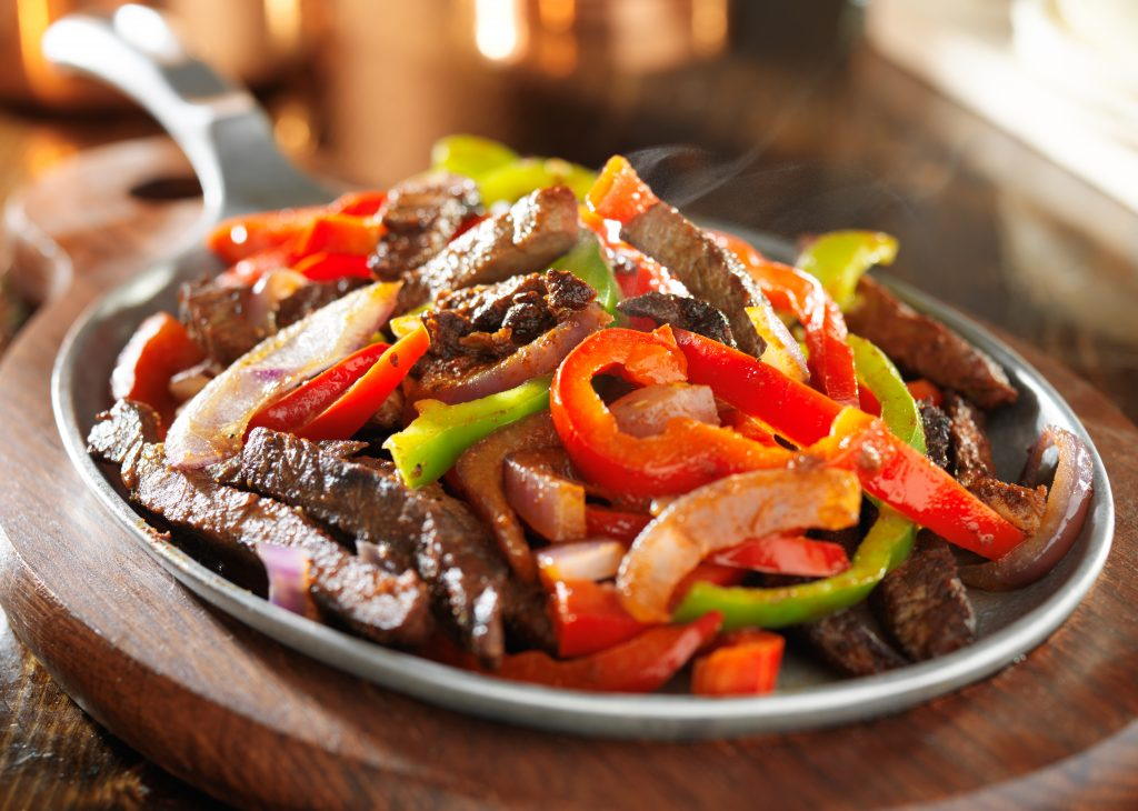 Skillet of steak fajitas with peppers, one of the most ubiquitous things to eat in Texas