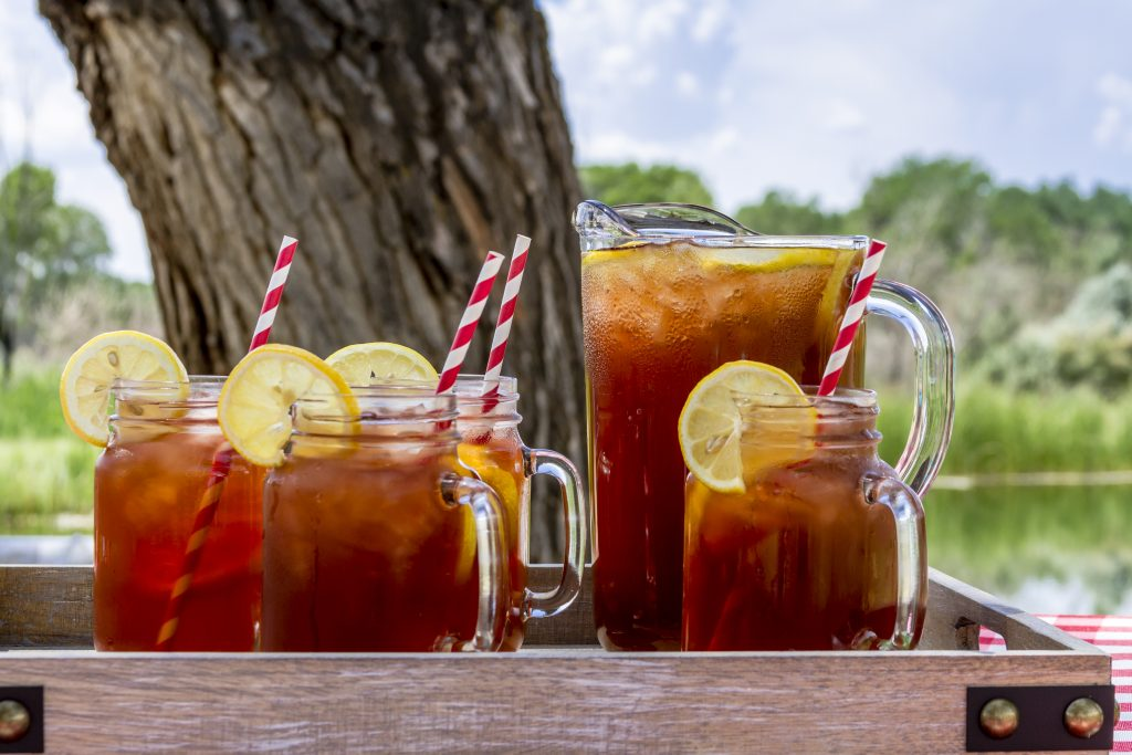 a pitcher of sweet tea and 4 glasses of sweet tea with slices of lemon on them sitting on a wooden tray outside on a table in front of a tree