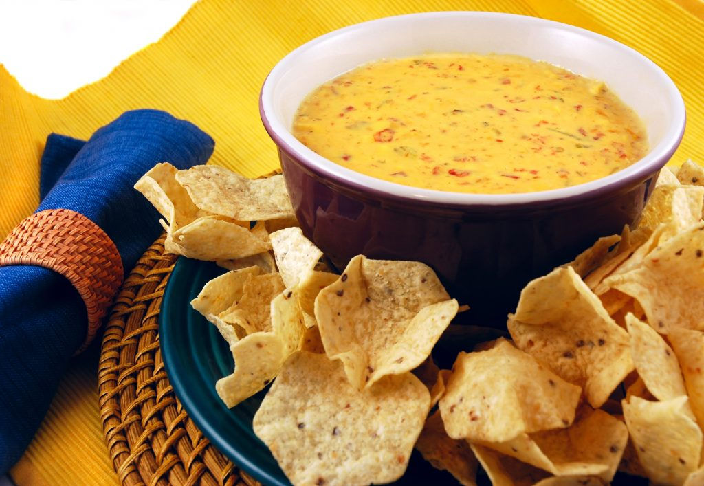 Bowl of chili con queso with tortilla chips on a plate in front of it