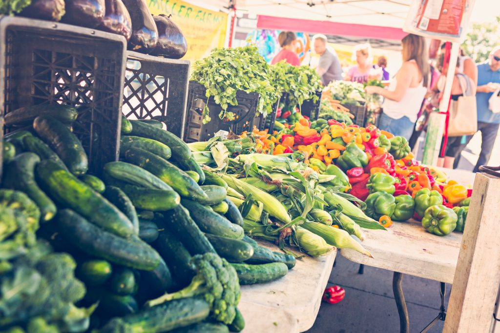 photo from a farmers market in texas with vegetables spilling out of crates onto a table. people shopping are in the background of the photo.